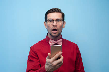 Portrait of a shocked young man with smartphone Фото со стока