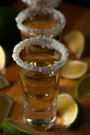 Mexican Tequila Gold in glasses with lime slices and salt.