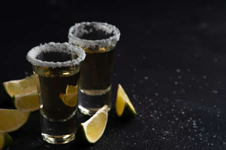 Mexican Gold Tequila with lime slices and salt.