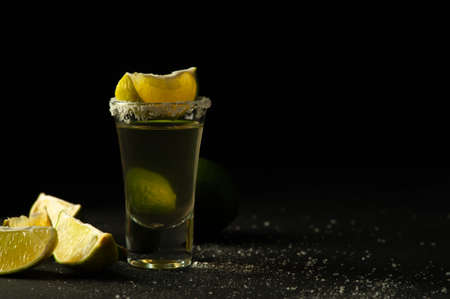 Gold Mexican Tequila shot with lime slice and salt.