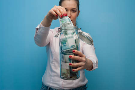 Young charming woman holds a jar with money