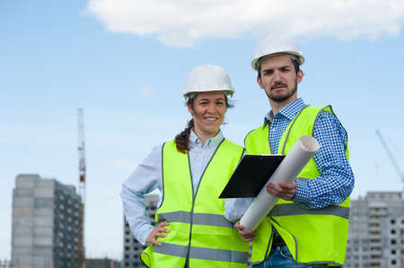 Two Young Engineers Man and Woman In Green Vests And Helmets