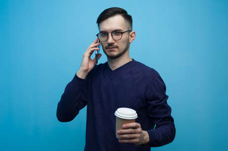 Handsome young man with coffee mug and smartphone