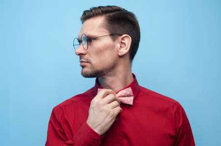 Close-up of the hands of a young man in a red shirt correcting bow-tie against a blue background. The concept of gallantry and style