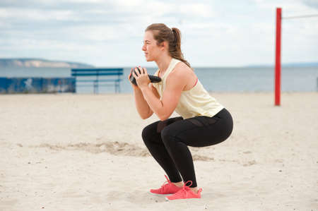 Portrait of positive woman wearing top and leggings warming up.