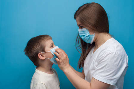 Portrait of caucasian mother and son wearing protective medical mask.