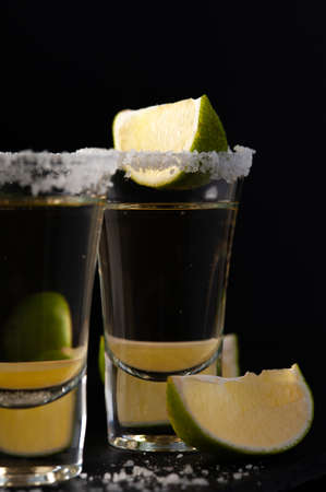 Shots of Mexican Gold Tequila with lime slices and salt. Imagens - 156633245