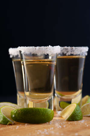 Shots of Mexican Gold Tequila with lime slices and salt.