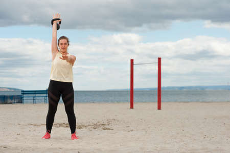 Woman weightlifting kettlebell weight at outdoor fitness gym. Imagens