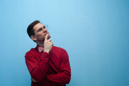 Portrait of thoughtful man in glasses and red shirt posing on blue background. Imagens