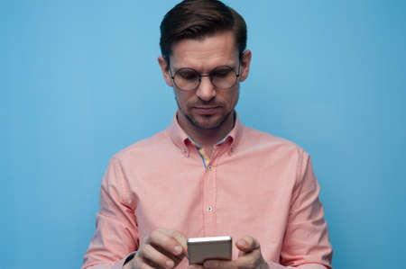 Portrait of a handsome young man in glasses scrolling social media in a smartphone