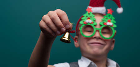 Portrait of happy little boy wearing headband with Santa Claus Hat and funny glasses with Christmas toys Imagens