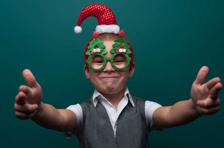 Portrait of happy cheerful boy wearing headband with Santa Claus Hat and funny glasses with Christmas trees Imagens - 156681587