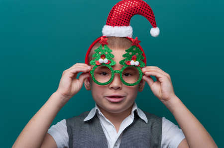 Portrait of little boy wearing headband with Santa Claus Hat and funny glasses with Christmas trees