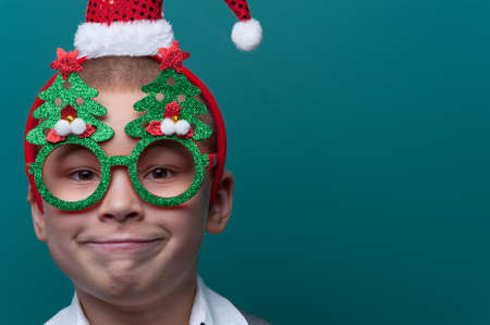 Portrait of happy cheerful boy wearing headband with Santa Claus Hat and funny glasses with Christmas trees Imagens - 156681591