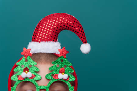 Close-up - Portrait of boy wearing headband with Santa Claus Hat and funny glasses with Christmas trees posing on green wall. Imagens - 156681593