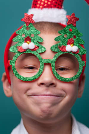 Portrait of happy little boy wearing headband with Santa Claus Hat and funny glasses with Christmas trees Imagens - 156681595