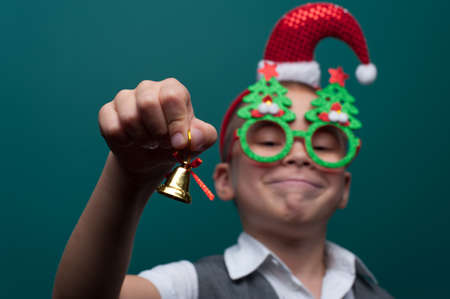 Portrait of happy little boy wearing headband with Santa Claus Hat and funny glasses with Christmas toys Standard-Bild