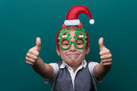 Portrait of happy cheerful boy wearing headband with Santa Claus Hat and funny glasses with Christmas trees