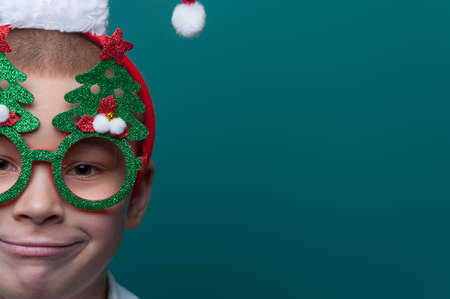 Portrait of happy little boy wearing headband with Santa Claus Hat and funny glasses with Christmas trees