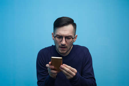 Portrait of young man in glasses looking at his smartphone