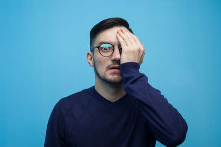 Portrait of young scared man covering his eye Imagens