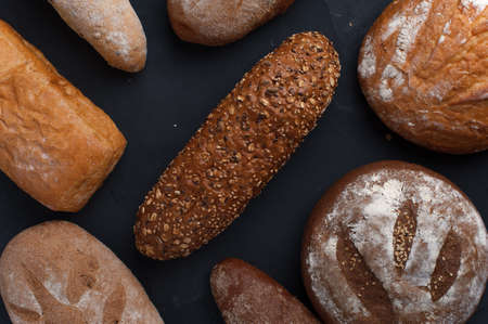 Different Freshly baked breads on dark table.