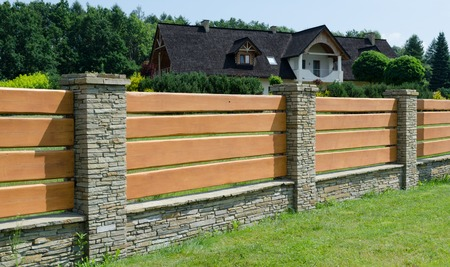 Durable fence made of wood and stone house enclosing Archivio Fotografico