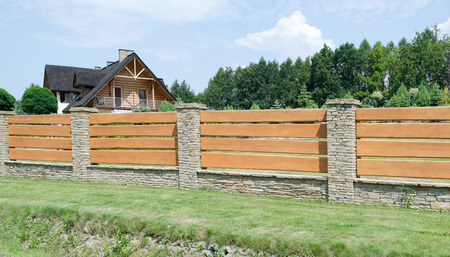 Durable fence made of wood and stone house enclosing Banco de Imagens
