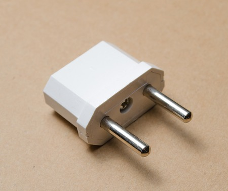 adapters: White EU plugs power adapters on a brown background