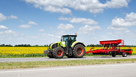 plough machine: Tractor rides on the road near the field Stock Photo