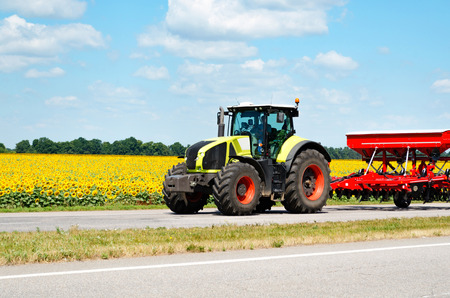 tractor: Tractor rides on the road near the field Stock Photo