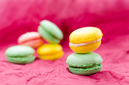 burgundy background: French macaroon colorful on burgundy background (green, yellow, pink) Stock Photo