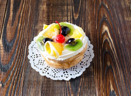 choux: Choux pastry with fruit on a wooden background. Rustic style.