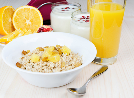 garnets: Breakfast of oatmeal with raisins and orange. Juice and yogurt with pomegranate on a white wooden table. Horizontal