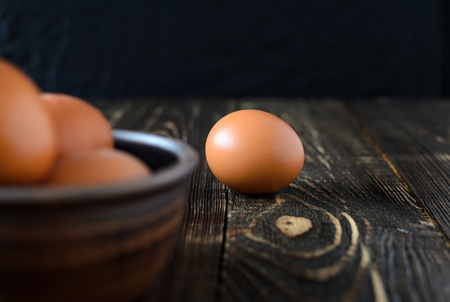 Fresh farm eggs in the bowl on a wooden rustic background Archivio Fotografico