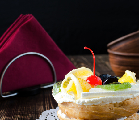 Choux pastry with fresh fruit on a white napkin. Wooden dark background.