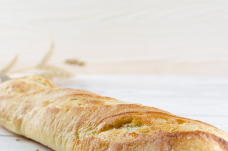 satisfying: White fresh baguette is light on wooden boards. Spikelets of wheat wrapped in burlap.
