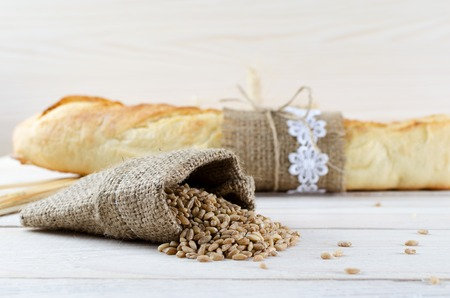 Sack of wheat grains on the background of fresh white baguette.
