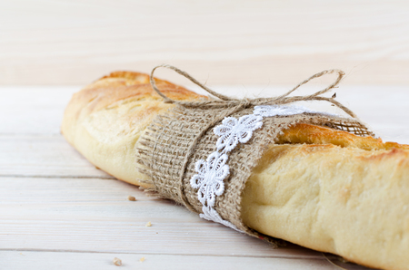 Fresh white baguette wrapped in burlap and tied with a rope.