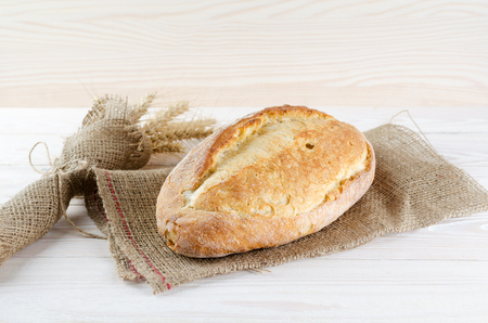 White fresh loaf on sacking with wheat spikelets. Archivio Fotografico