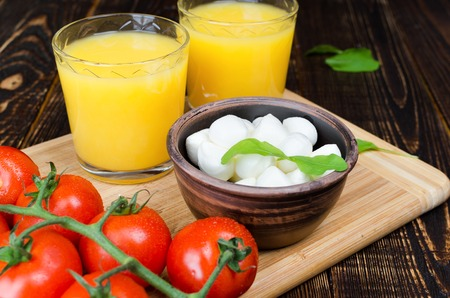 Orange juice, mozzarella and tomatoes on a wooden table. Horizontal. Archivio Fotografico