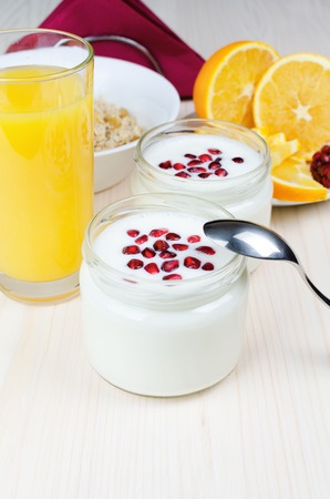 White yogurt with red pomegranate seeds. On a white wooden table. Vertical.