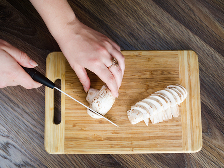 The girl cuts mushrooms on white chopping board of wood. Top view