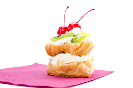 Choux pastry with fruit on burgundy napkin. Cherry, kiwi, orange and grapes. On a white background.