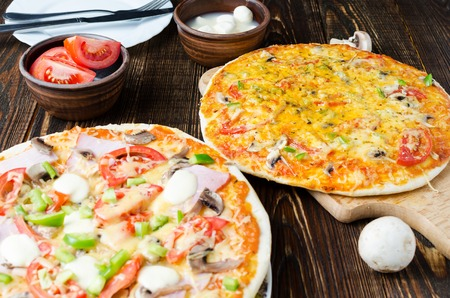 Two of pizza with tomatoes, mushrooms and cheese. Laid wooden table. Archivio Fotografico