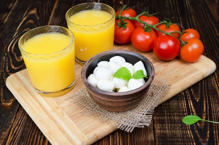 Mozzarella in a clay bowl with orange juice and tomatoes on a branch lying on a wooden kitchen board. Archivio Fotografico