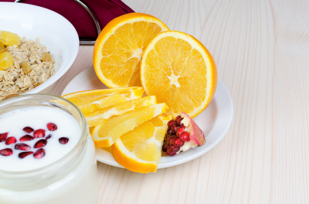 garnets: Sliced orange with pomegranate seeds and yogurt. Covered wooden white table. Stock Photo