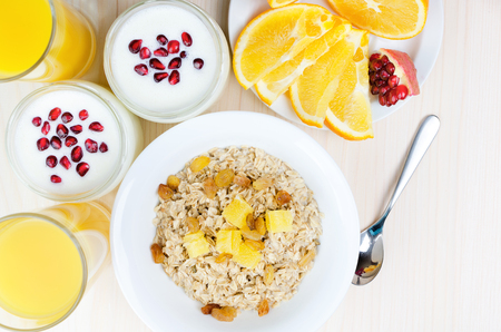 oatmeal: Morning healthy breakfast. Oatmeal with fruit, yogurt with pomegranate, orange slices and fresh juice.