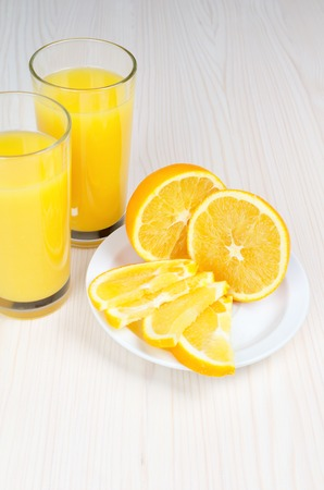 Orange juice in a glass. Slices of orange on a plate on a white wooden table. Archivio Fotografico